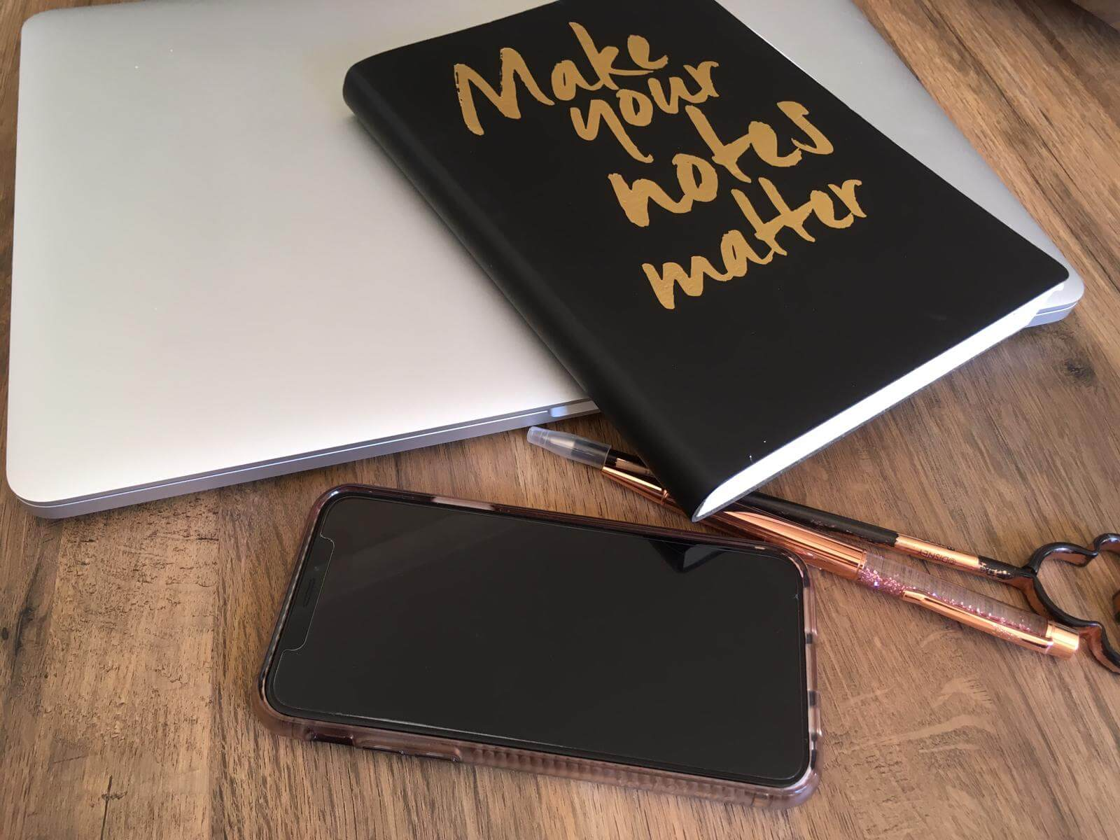 Note pad, laptop, pen, and phone image on a table